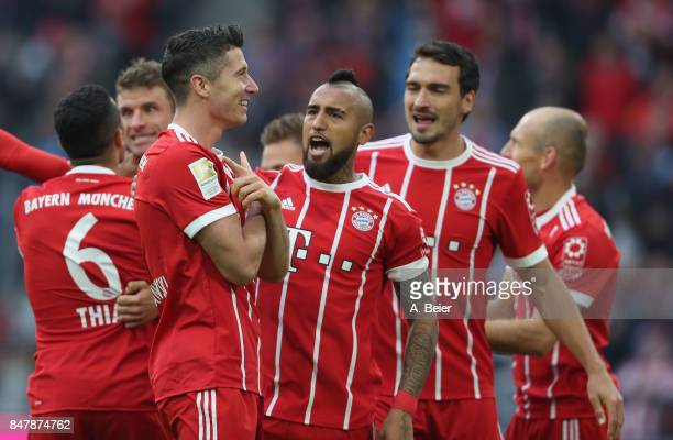 Robert Lewandowski of FC Bayern Muenchen celebrates his first goal with teammate Arturo Vidal and Mats Hummels during the Bundesliga match between FC...