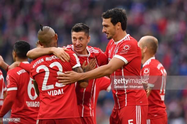 Robert Lewandowski of FC Bayern Muenchen celebrates scoring his teams third goal with Arturo Vidal and Mats Hummels during the Bundesliga match...