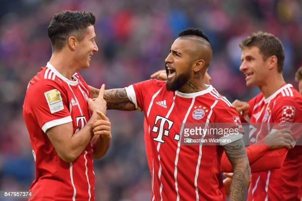 Robert Lewandowski of FC Bayern Muenchen celebrates scoring his teams third goal with Arturo Vidal during the Bundesliga match between FC Bayern...
