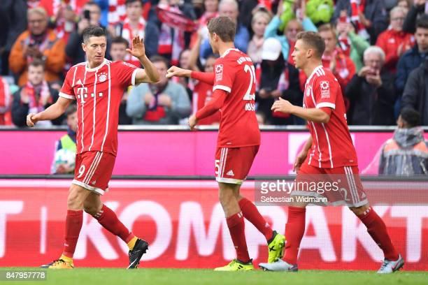 Robert Lewandowski of FC Bayern Muenchen celebrates scoring his teams fourth goal with teammates Thomas Mueller and Joshua Kimmich during the...