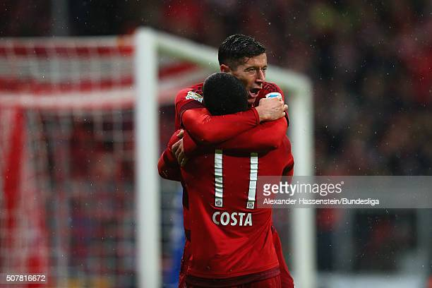 Robert Lewandowski of FC Bayern Muenchen celebrates scoring the opening goal with his team mate Douglas Costa during the Bundesliga match between FC...
