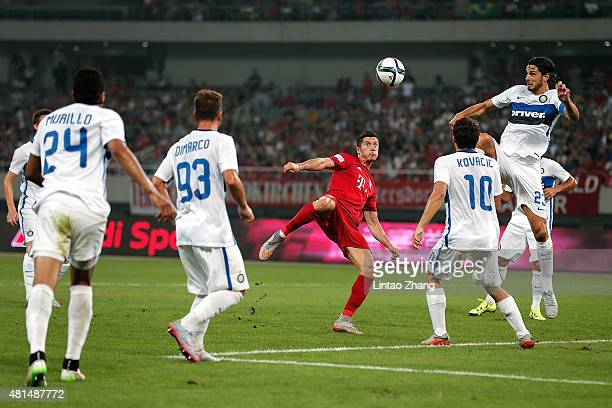 Robert Lewandowski of FC Bayern Muenchen challenges Andrea Ranocchia and Mateo Kovacic of FC Internazionale during the international friendly match...