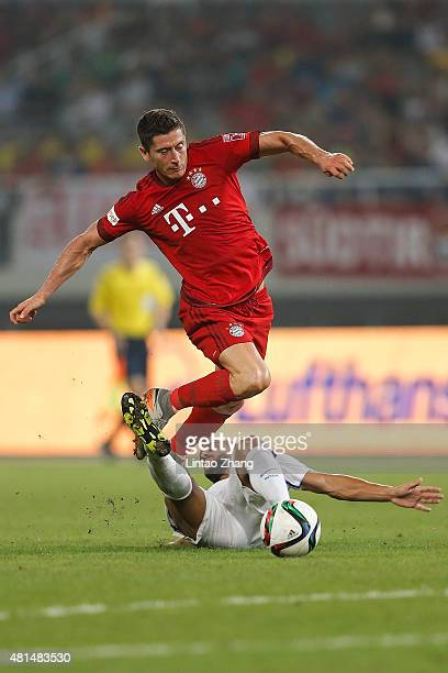 Robert Lewandowski of FC Bayern Muenchen challenges Martin Montoya of FC Internazionale during the international friendly match between FC Bayern...