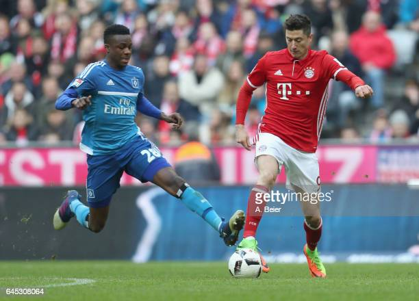 Robert Lewandowski of FC Bayern Muenchen fights for the ball with Gideon Jung of Hamburger SV during the Bundesliga match between Bayern Muenchen and...