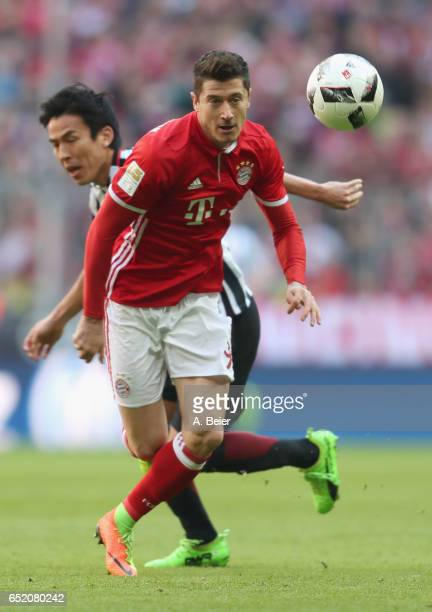 Robert Lewandowski of FC Bayern Muenchen fights for the ball with Makoto Hasebe of Eintracht Frankfurt during the Bundesliga match between Bayern...