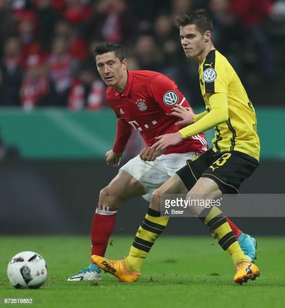 Robert Lewandowski of FC Bayern Muenchen fights for the ball with Julian Weigl of Borussia Dortmund during the DFB Cup semi final match between FC...