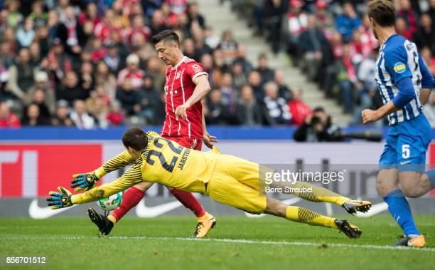 Robert Lewandowski of FC Bayern Muenchen is challenged by goalkeeper Rune Jarstein of Hertha BSC during the Bundesliga match between Hertha BSC and...