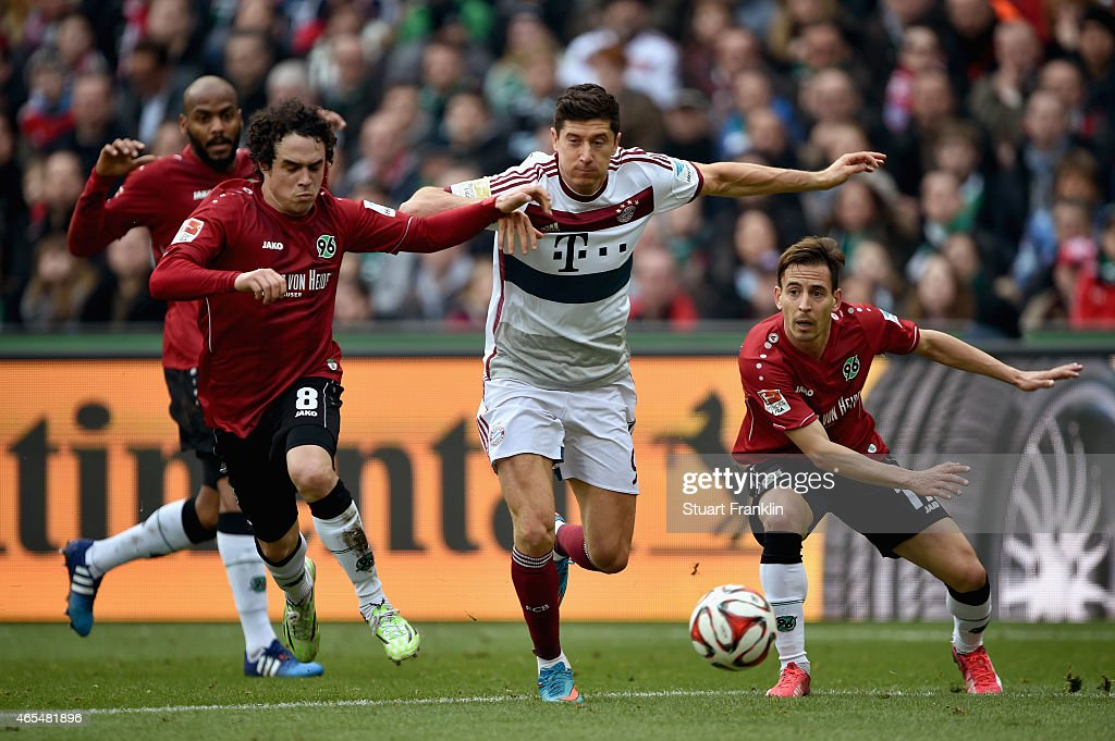 Robert Lewandowski of FC Bayern Muenchen is chased by Manuel Schmiedebach and Joao Pedro da Silva Pereira of Hannover 96 during the Bundesliga match between Hannover 96 and FC Bayern Muenchen at HDI-Arena on March 7, 2015 in Hanover, Germany.