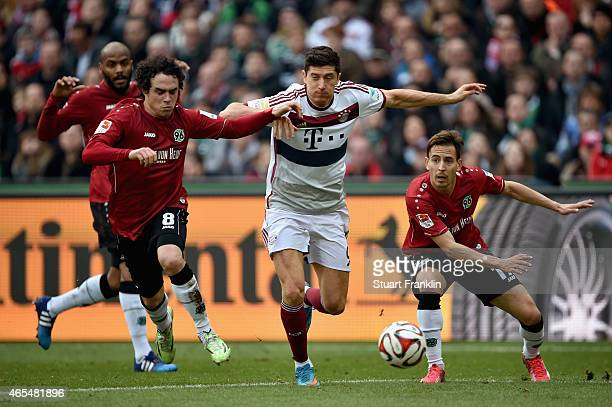Robert Lewandowski of FC Bayern Muenchen is chased by Manuel Schmiedebach and Joao Pedro da Silva Pereira of Hannover 96 during the Bundesliga match...