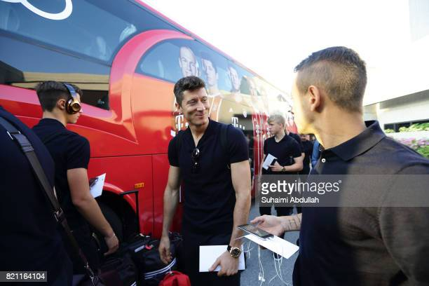 Robert Lewandowski of FC Bayern Muenchen prepares to board the team bus after arriving at Jet Quay Private Terminal ahead of the International...