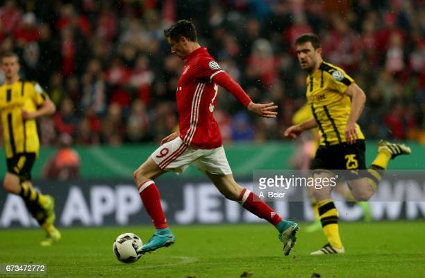 Robert Lewandowski of FC Bayern Muenchen runs with the ball during the DFB Cup semi final match between FC Bayern Muenchen and Borussia Dortmund at...