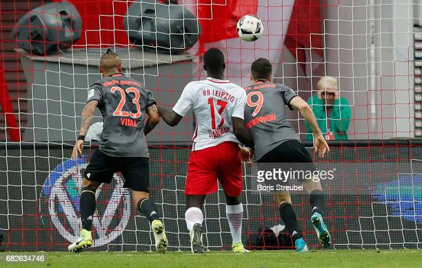 Robert Lewandowski of FC Bayern Muenchen scores his team's third goal against goalkeeper Peter Gulacsi of RB Leipzig during the Bundesliga match...