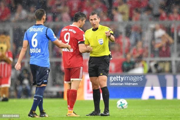 Robert Lewandowski of FC Bayern Muenchen talks to referee Tobias Stieler after the Bundesliga match between FC Bayern Muenchen and Bayer 04...