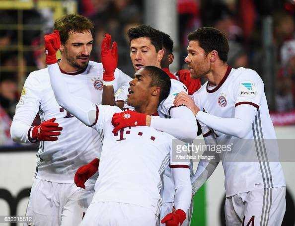 Robert Lewandowski of Muechen celebrates scoring his goal with Douglas Costa Mats Hummels and Xabi Alonso during the Bundesliga match between SC...