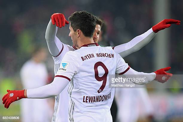 Robert Lewandowski of Muechen celebrates with Xabi Alonso after the Bundesliga match between SC Freiburg and Bayern Muenchen at SchwarzwaldStadion on...