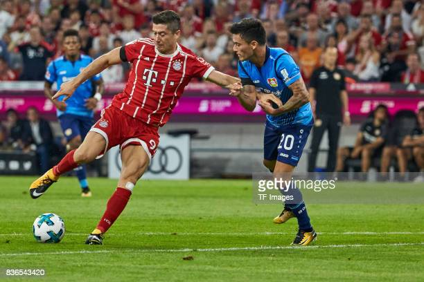 Robert Lewandowski of Muenchen and Charles Aranguiz battle for the ball during the Bundesliga match between FC Bayern Muenchen and Bayer 04...