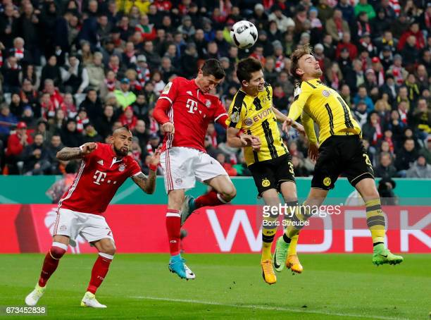 Robert Lewandowski of Muenchen and Julian Weigl of Dortmund head for the bal during the DFB Cup semi final match between FC Bayern Muenchen and...