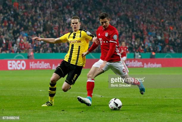 Robert Lewandowski of Muenchen and Sven Bender of Dortmund battle for the bal during the DFB Cup semi final match between FC Bayern Muenchen and...