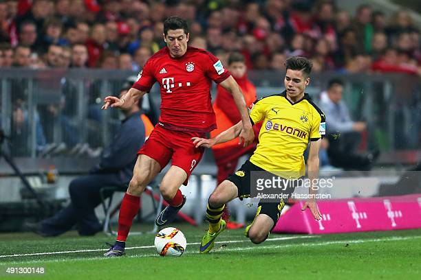 Robert Lewandowski of Muenchen battles for the ball with Julian Weigl of Dortmund during the Bundesliga match between FC Bayern Muenchen and BVB...