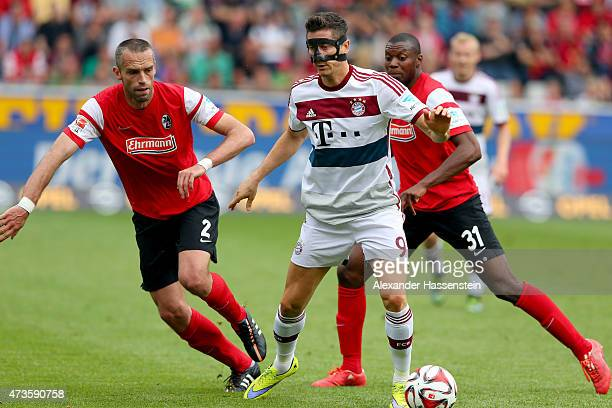 Robert Lewandowski of Muenchen battles for the ball with Pavel Krmas of Freiburg and his team mate Karim Guede during the Bundesliga match between...