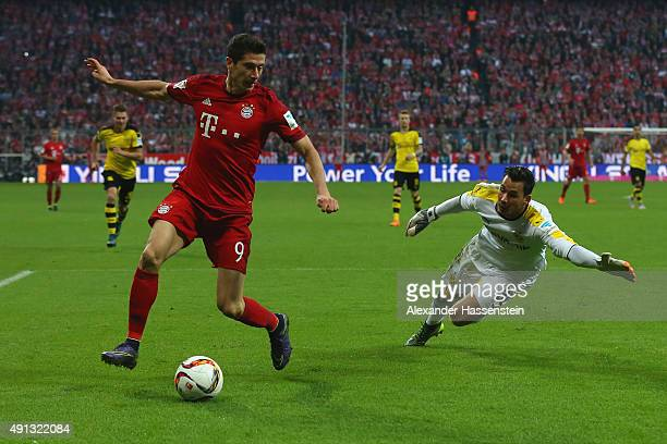 Robert Lewandowski of Muenchen battles for the ball with Roman Buerki keeper of Dortmund during the Bundesliga match between FC Bayern Muenchen and...