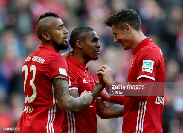 Robert Lewandowski of Muenchen celebrate with team mate Arturo Vidal and Douglas Costa after he scores the 3rd goal during the Bundesliga match...