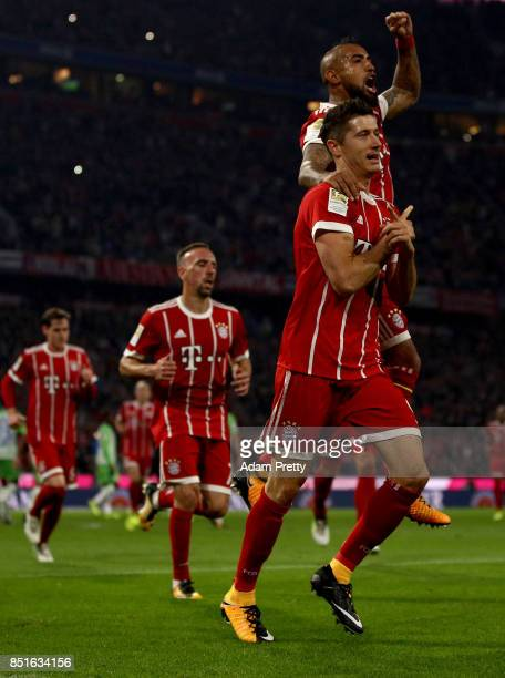 Robert Lewandowski of Muenchen celebrate with team mate Arturo Vidal after he scores the opening goal by penalty kick during the Bundesliga match...