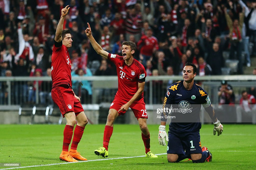 Robert Lewandowski of Muenchen celebrates his team's first goal with team mate Thomas Mueller as goalkeeper Diego Benaglio of Wolfsburg reacts during the Bundesliga match between FC Bayern Muenchen and VfL Wolfsburg at Allianz Arena on September 22, 2015 in Munich, Germany.