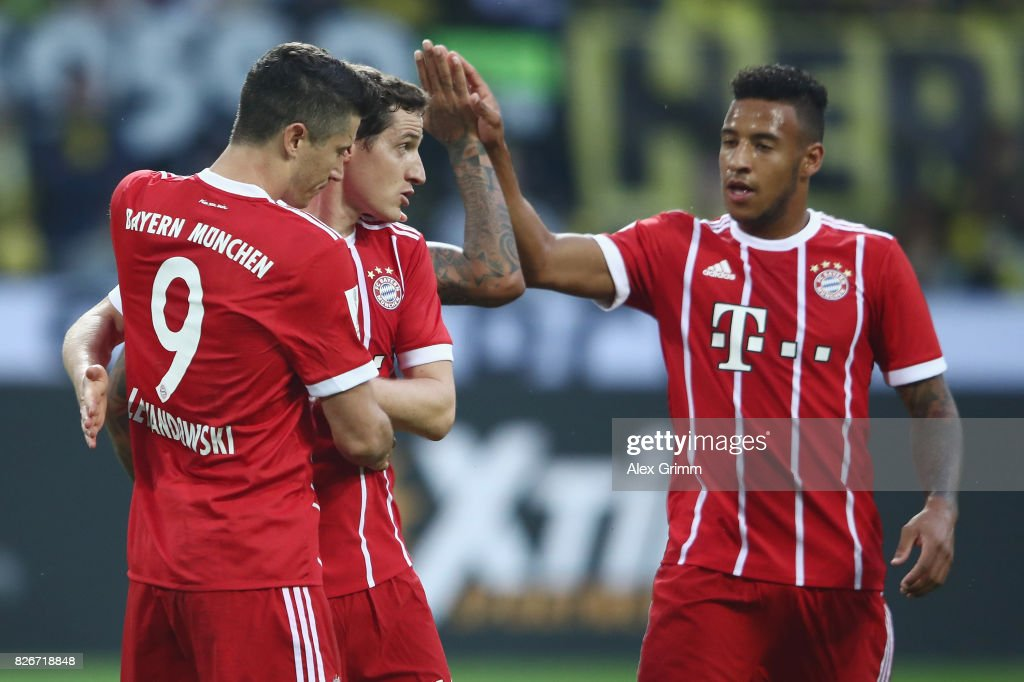 Robert Lewandowski of Muenchen celebrates his team's first goal with team mates Sebastian Rudy and Corentin Tolisso (L-R) during the DFL Supercup 2017 match between Borussia Dortmund and Bayern Muenchen at Signal Iduna Park on August 5, 2017 in Dortmund, Germany.