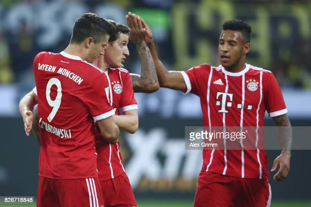 Robert Lewandowski of Muenchen celebrates his team's first goal with team mates Sebastian Rudy and Corentin Tolisso during the DFL Supercup 2017...