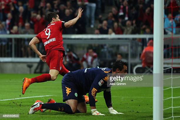 Robert Lewandowski of Muenchen celebrates his team's fourth goal as goalkeeper Diego Benaglio of Wolfsburg reacts during the Bundesliga match between...