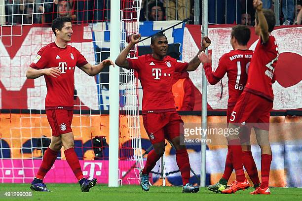 Robert Lewandowski of Muenchen celebrates his team's fourth goal with team mates Douglas Costa Mario Goetze and Thomas Mueller during the Bundesliga...