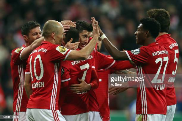 Robert Lewandowski of Muenchen celebrates his team's third goal with team mates during the DFB Cup quarter final between Bayern Muenchen and FC...