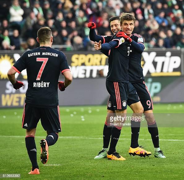 Robert Lewandowski of Muenchen celebrates scoring his goal with Thomas Mueller and Franck Ribery during the Bundesliga match between VfL Wolfsburg...