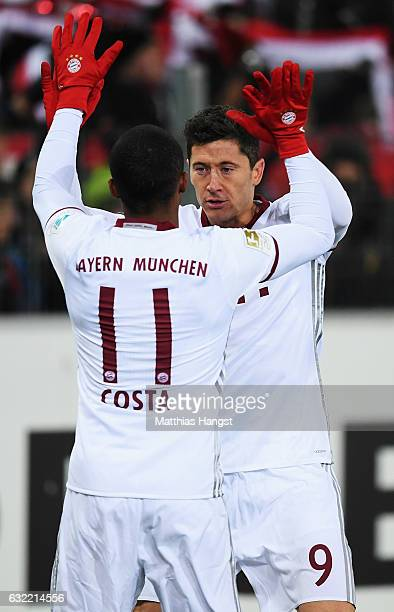 Robert Lewandowski of Muenchen celebrates scoring his goal with Douglas Costa during the Bundesliga match between SC Freiburg and Bayern Muenchen at...