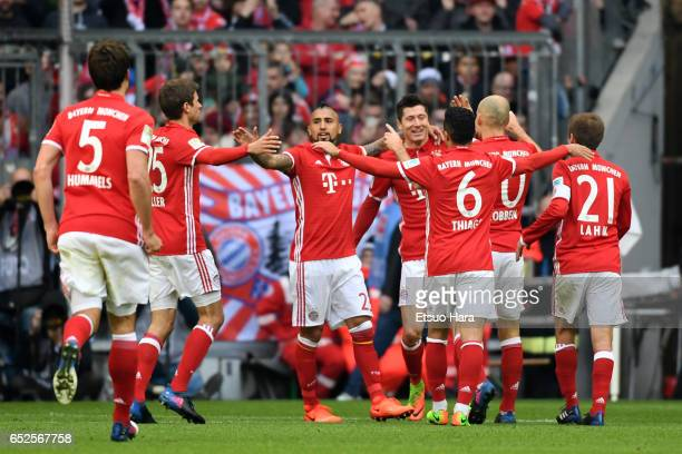 Robert Lewandowski of Muenchen celebrates scoring his side's third goal with his team mates during the Bundesliga match between Bayern Muenchen and...