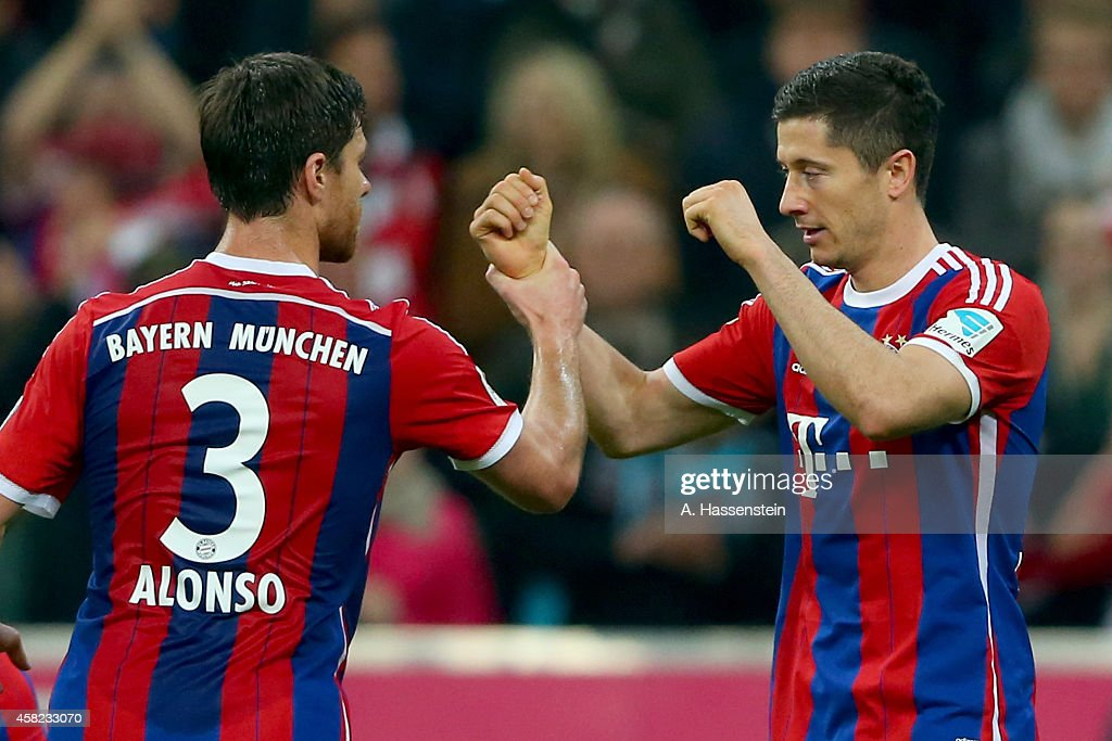 Robert Lewandowski of Muenchen celebrates scoring the first team goal with his team mate Xabi Alonso during the Bundesliga match between FC Bayern...