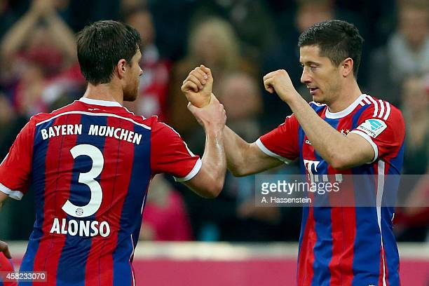 Robert Lewandowski of Muenchen celebrates scoring the first team goal with his team mate Xabi Alonso during the Bundesliga match between FC Bayern...
