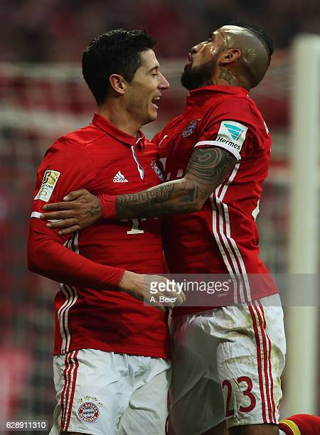 Robert Lewandowski of Muenchen celebrates scoring the second goal with Arturo Vidal during the Bundesliga match between Bayern Muenchen and VfL...