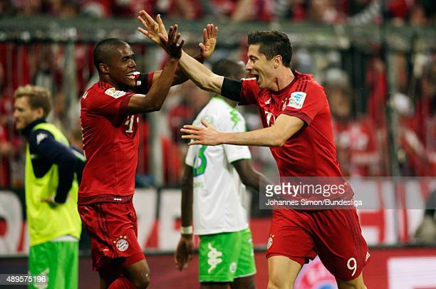 Robert Lewandowski of Muenchen celebrates with team mate Douglas Costa after scoring his team's 4th goal during the Bundesliga match between FC...