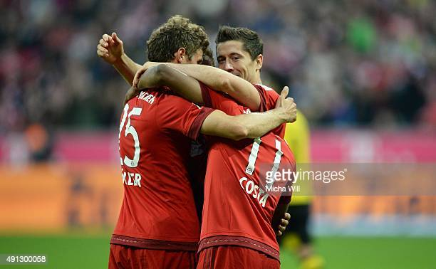 Robert Lewandowski of Muenchen celebrates with teammates after scoring his team's fourth goal during the Bundesliga match between FC Bayern Muenchen...