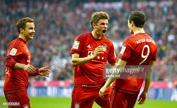 Robert Lewandowski of Muenchen celebrates with Thomas Mueller of Muenchen and Mario Goetze of Muenchen after scoring his team's third goal during the...