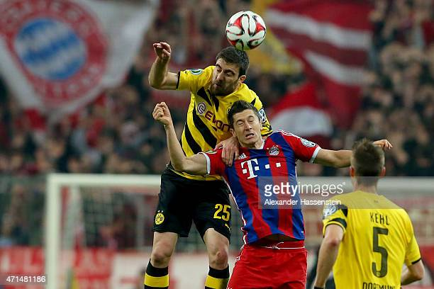 Robert Lewandowski of Muenchen challenges for the ball with Sokratis Papastathopoulos of Dortmund during the DFB Cup Semi Final match between FC...