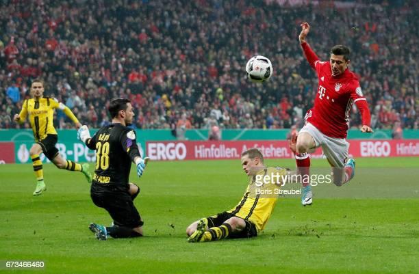 Robert Lewandowski of Muenchen fails to score over Roman Buerki goalkeeper of Dortmund battle during the DFB Cup semi final match between FC Bayern...