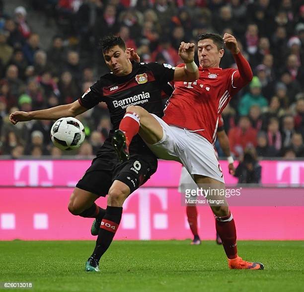 Robert Lewandowski of Muenchen is challenged by Aleksandar Dragovic of Leverkusen during the Bundesliga match between Bayern Muenchen and Bayer 04...