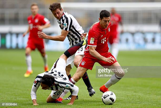 Robert Lewandowski of Muenchen is challenged by David Abraham of Eintracht Frankfurt and Makoto Hasebe of Eintracht Frankfurt during the Bundesliga...