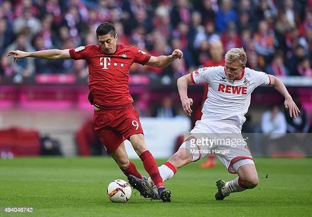 Robert Lewandowski of Muenchen is challenged by Frederik Sorensen of Koeln during the Bundesliga match between FC Bayern Muenchen and 1 FC Koeln at...