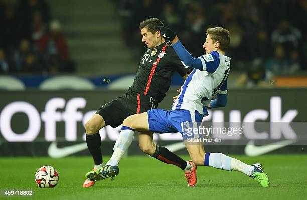 Robert Lewandowski of Muenchen is challenged by Jens Hegeler of Berlin during the Bundesliga match between Hertha BSC and FC Bayern Muenchen at...