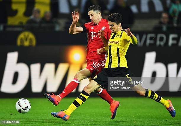 Robert Lewandowski of Muenchen is challenged by Marc Bartra of Dortmund during the Bundesliga match between Borussia Dortmund and Bayern Muenchen at...
