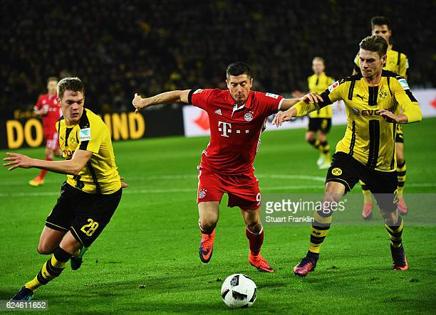 Robert Lewandowski of Muenchen is challenged by Matthias Ginter and Lukasz Piszczek of Dortmund during the Bundesliga match between Borussia Dortmund...